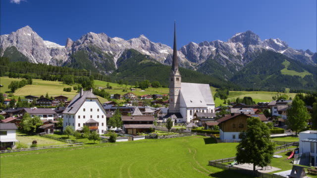 wide aerial shot of houses and tower near mountain range / maria alm, austria - alm stock-videos und b-roll-filmmaterial