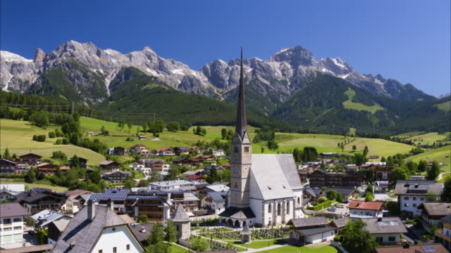wide aerial shot of houses and tower near mountain range / maria alm,, austria - alm stock-videos und b-roll-filmmaterial