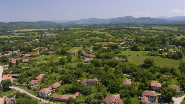 Wide aerial shot of houses in rural town near mountain range / Kapinovo, Bulgaria