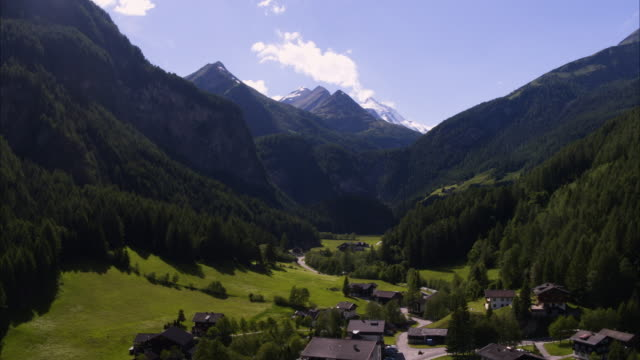wide aerial shot of houses in rural valley town / heiligenblut, austria - austria stock videos and b-roll footage