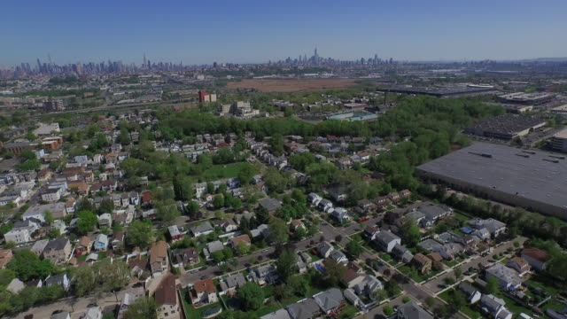 vídeos de stock e filmes b-roll de wide aerial shot of new jersey suburb, moving toward nyc skyline on the horizon - nova jersey