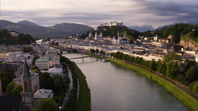 wide aerial shot of river in city at sunset / salzburg, austria - austria video stock e b–roll