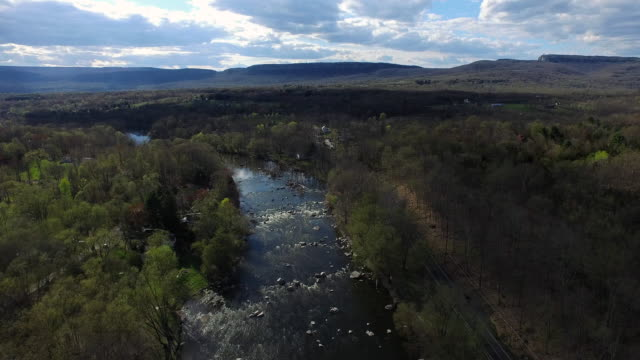 wide aerial shot of rocky river surrounded by trees, moving toward blue hills on a cloudy day - アルスター郡点の映像素材/bロール