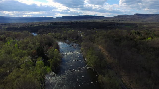 wide aerial shot of rocky river surrounded by trees, moving toward blue hills on a cloudy day - new paltz stock videos and b-roll footage