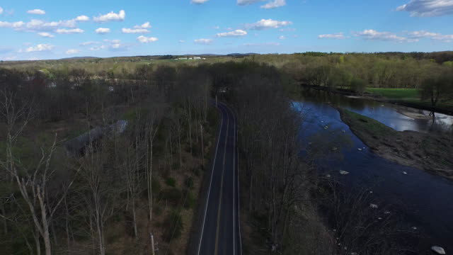 wide aerial shot pulling back and higher along one lane road running along rocky river - contea di ulster stato di new york video stock e b–roll