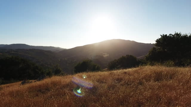 wide aerial, sun shines over mountains in california - wide stock-videos und b-roll-filmmaterial