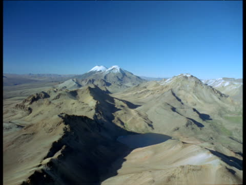 wide aerial track over andes mountain range, blue sky above - bolivia stock videos & royalty-free footage