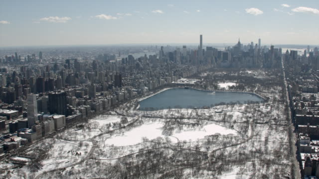 wide aerial view of central park with snow on a sunny winter day - central park manhattan stock videos & royalty-free footage