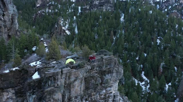 wide aerial view of couple sitting on top of cliff they climbed to camp - american fork canyon点の映像素材/bロール