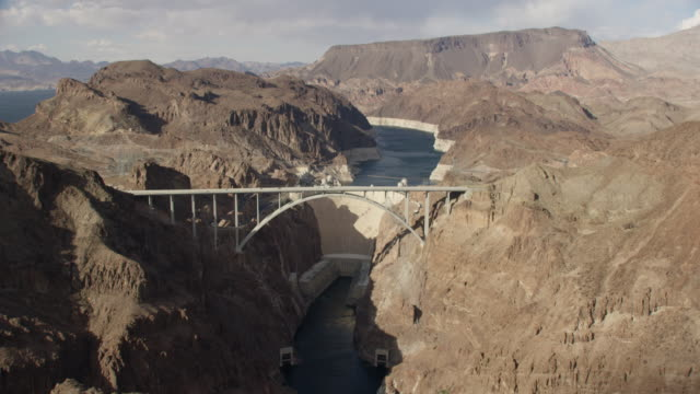 wide aerial view of the hoover dam and mike o'callaghan–pat tillman memorial bridge - hydroelectric power stock videos and b-roll footage