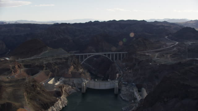 wide aerial view of the hoover dam and mike o'callaghan–pat tillman memorial bridge - ネバダ州クラーク郡点の映像素材/bロール