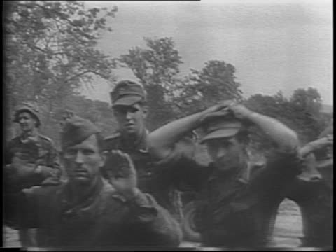 vidéos et rushes de wide and close up corporal earl mcallister sitting at a large piece of equipment's steering position / montage of surrendering german soldiers... - prisonnier de guerre