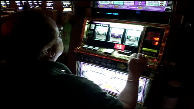 wide and close up of people playing slot machine in las vegas - fruit machine stock videos & royalty-free footage