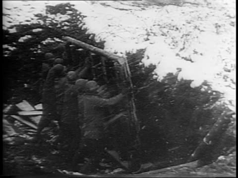 vidéos et rushes de wide and medium shot of allied soldiers cutting down a tree in the snow / medium shots of soldiers building in the snowy trenches / military vehicles... - infanterie