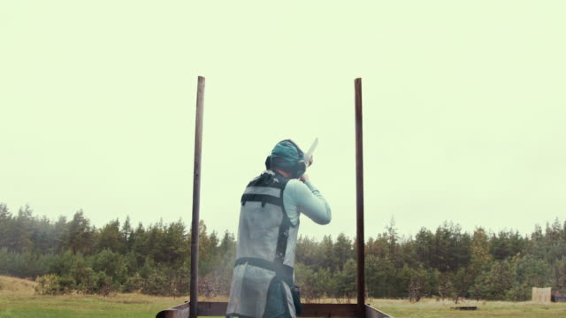 wide angel shot of a compak shooter (slow motion) - clay pigeon shooting stock videos and b-roll footage