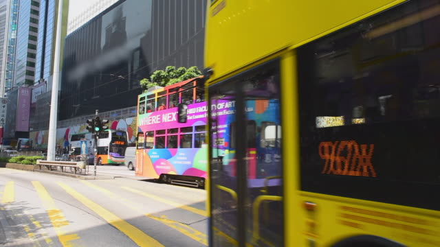 wide angle: a bus and double decker tram driving in hong kong - tram stock-videos und b-roll-filmmaterial