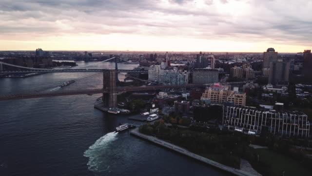 vídeos de stock, filmes e b-roll de wide angle aerial shot of new york city's manhattan bridge, brookly bridge, and east river at sunrise - rio east