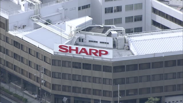 Wide angle aerial view of the Sharp's headquarters complex in Abenoku Osaka Zooming in on the logo of Sharp on the top of the building Zooming out as...