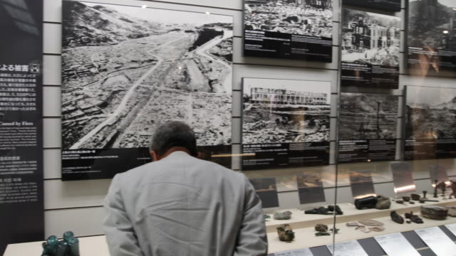 Wide angle at the Atomic Bomb Museum Nagasaki a man is looking at photographs displaying the destruction of the town and the explosion of the Atomic...