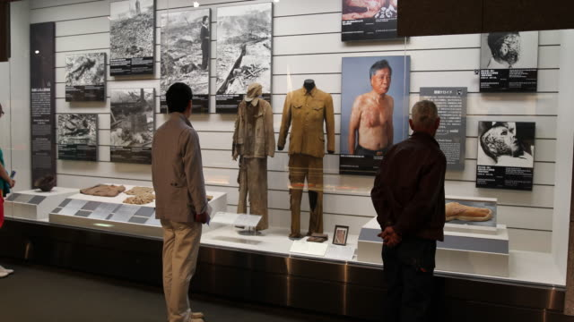 vidéos et rushes de wide angle, at the atomic bomb museum nagasaki, several people in front of a showcase displaying several injuries from people after the disaster. - arme de destruction massive