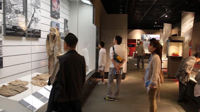 vidéos et rushes de wide angle, at the atomic bomb museum nagasaki, several visitors are looking at variant showcases. - arme de destruction massive