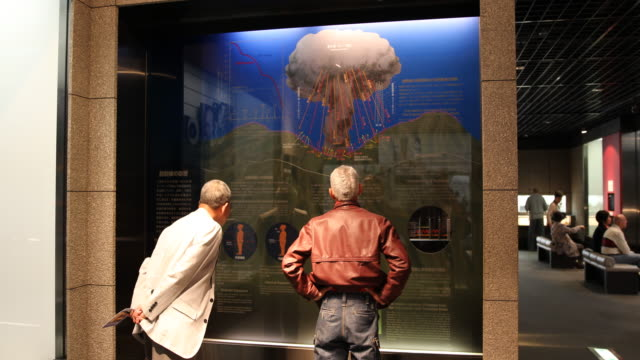 wide angle at the atomic bomb museum nagasaki two visitors are looking at a illustration that explains the technical details about the explosion of... - radioaktiver niederschlag stock-videos und b-roll-filmmaterial