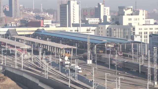 railroad tracks stretching out from urumqi south railway station zooming in on the local trains running slowly into the station - xinjiang province stock videos & royalty-free footage