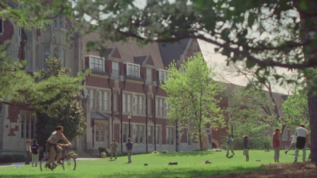 wide angle college age men throwing tossing a frisbee on university campus. hacky sack soccer football  then see medium long shot est all boy's men's academy school institution. three story gothic-style red brick building with green lawn and trees. could