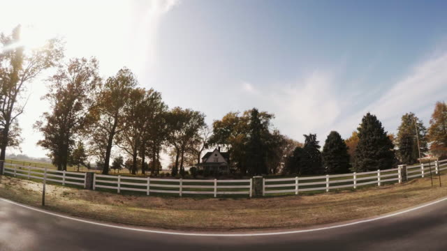Wide angle drive by of a small farm house surrounded by a white rail fence and fertile farm fields with a huge blue sky.