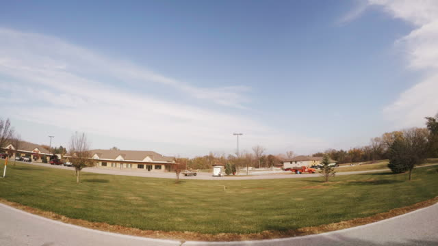 wide angle drive by of a small town strip mall. - centro commerciale suburbano video stock e b–roll