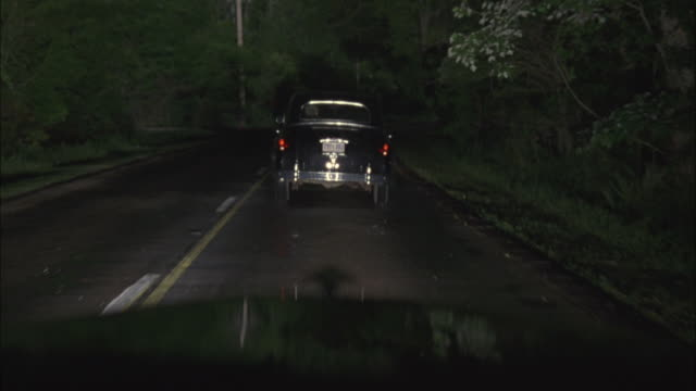 wide angle driving pov straight forward in vintage car following another vintage car on rural area two lane road. headlights shine. camera car passes second car, has to swerve out of the way of an oncoming car. - headlight stock videos & royalty-free footage