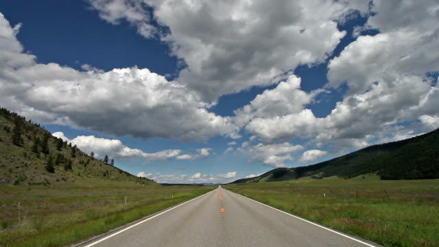 wide angle pov of empty highway on prairie and mountain landscape with puffy white clouds in sky. - empty road stock videos and b-roll footage