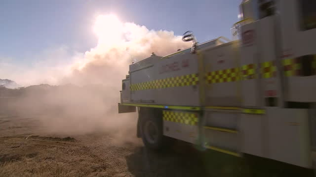 wide angle establishing shot of a fire truck driving down a dusty dirt road in australia and a cloud of smoke can be seen on the horizon. - environment or natural disaster or climate change or earthquake or hurricane or extreme weather or oil spill or volcano or tornado or flooding stock videos & royalty-free footage