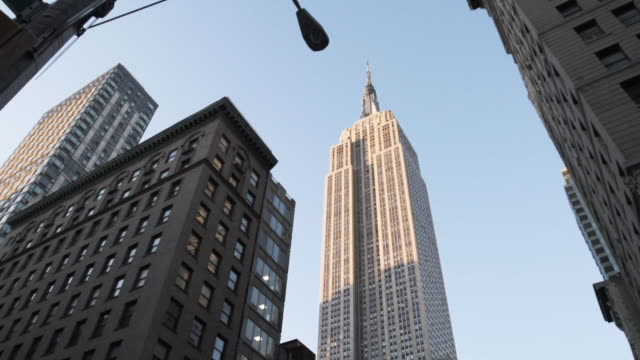 wide angle, establishing shot of new york city's empire state building at sunset. - empire state building video stock e b–roll