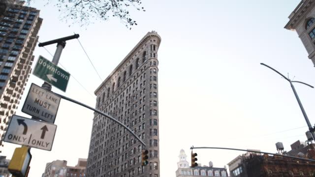 wide angle establishing shot of new york city's flatiron building on a warm autumn afternoon. - flatiron building manhattan stock videos & royalty-free footage