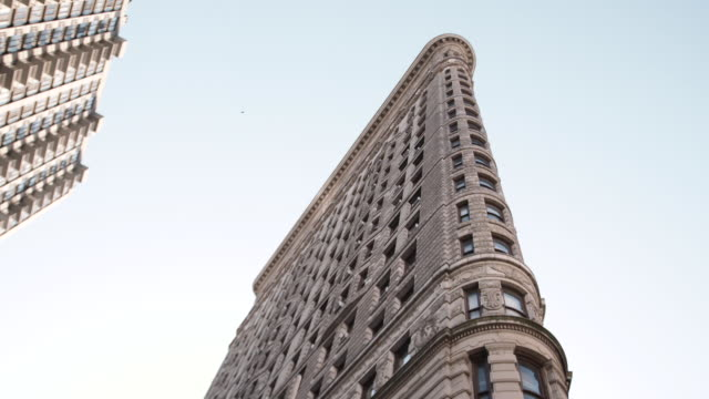 wide angle establishing shot of new york city's flatiron building on a warm autumn afternoon. - flatiron building manhattan stock videos and b-roll footage