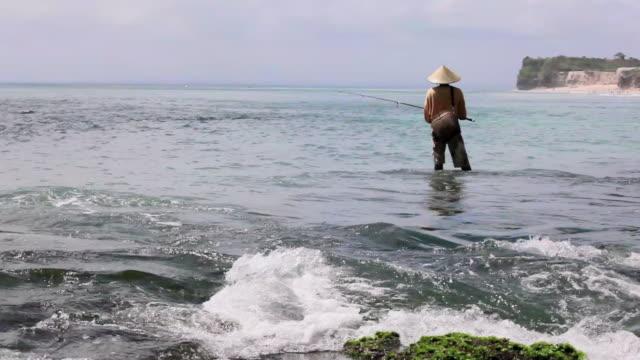 vídeos y material grabado en eventos de stock de wide angle: fisherman waiting patiently at keramas - ancho
