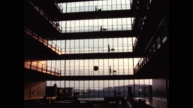 1962 - wide angle five stories of glass corridors five women synchronously push research carts - large stock videos & royalty-free footage