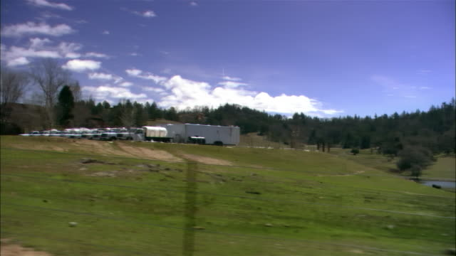 Wide angle POV from moving car, trucks in parking lot on farm