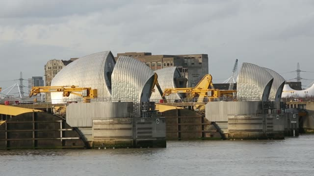wide angle general view the thames barrier the flood defence system protecting london with skyscraper office towers beyond in the canary wharf... - dome stock videos & royalty-free footage