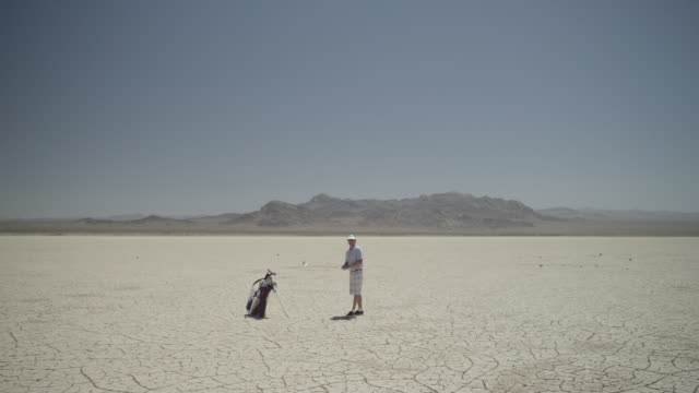 Wide angle, Golfer on dry lake selects club and positions himself to take a his shot.