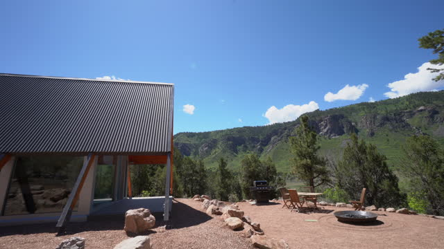wide angle handheld side angle shot of a modern xeriscaped tiny home in western colorado - modern rock stock videos & royalty-free footage