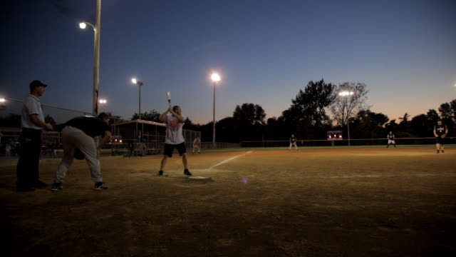 wide angle hometown baseball diamond at night, the batter hits the soft ball to left field. - batting stock videos & royalty-free footage