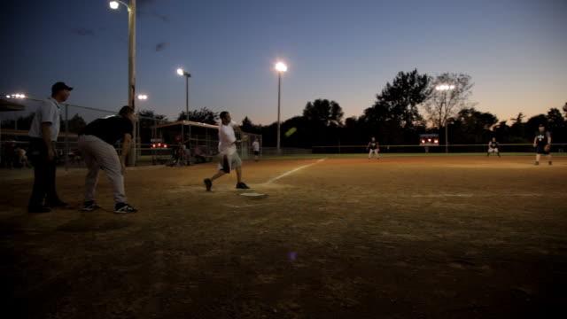 Wide angle hometown baseball diamond at night, the batter hits the softball.