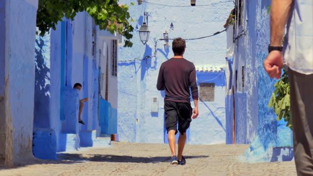 Wide Angle: Man Walking Away on Cobblestone Street