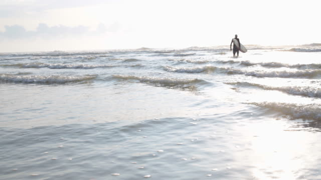 wide angle mature male surfer walking into sea carrying surfboard - senior men stock videos & royalty-free footage