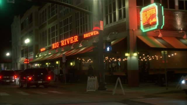 wide angle moving pov of bars and restaurants in downtown area. neon signs, pedestrians, and city streets.