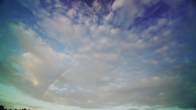 Wide angle of a beautiful blue sky, white clouds and a rainbow.