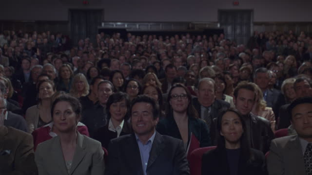 wide angle of audience in theater or auditorium. crowd of men and women is dressed in suits. audience is standing and then sits down, clapping and smiling. audience appears to be watching a theatrical performance. clip matches 3038-040.