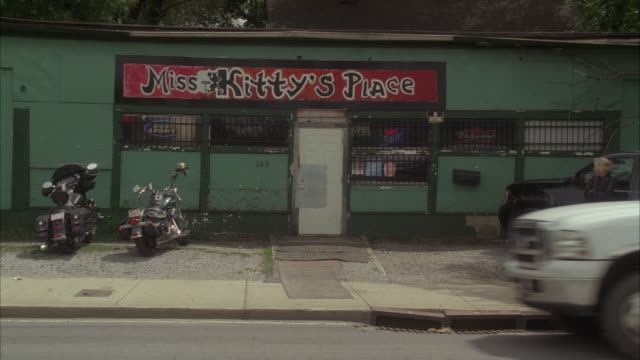 wide angle of bar with sign for miss kitty's place. two motorcycles parked in front. lower class. - bar点の映像素材/bロール